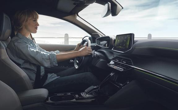 En kvinne kjører Peugeot e-208