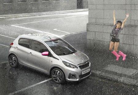 Kvinne hopper ved siden av en Peugeot 108 i regnet